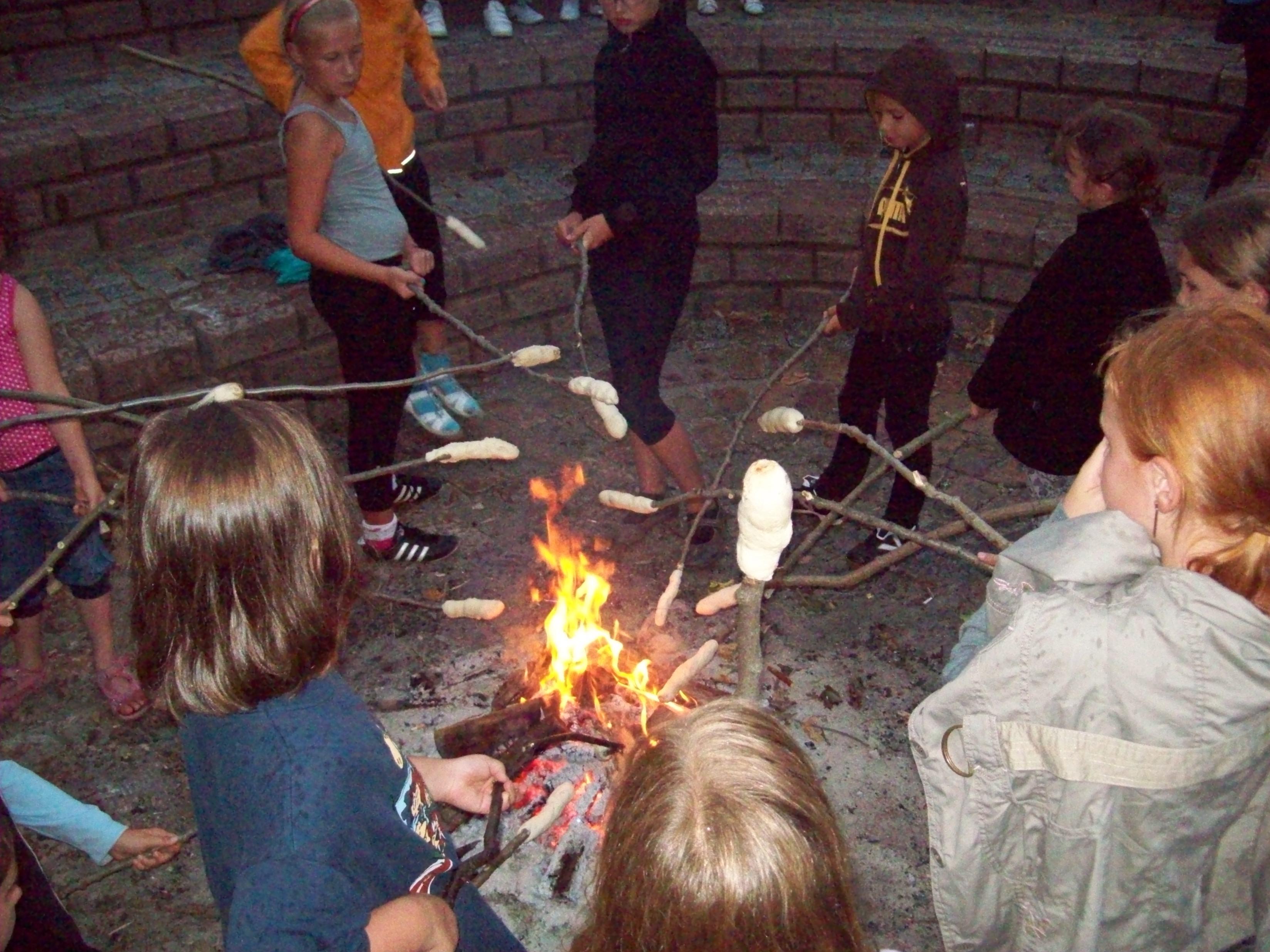 Kinder backen ihr Stockbrot am Lagerfeuer